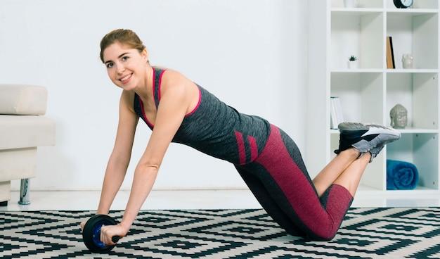 Mujer joven de la aptitud feliz que hace ejercicios en el gimnasio con la diapositiva de rodillo