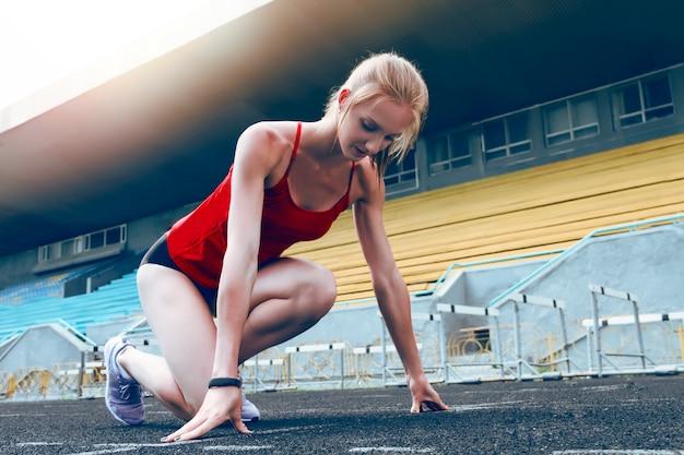 Mujer joven de la aptitud en la línea de salida de la pista del estadio