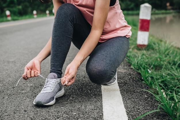 Mujer joven de la aptitud que ata las zapatillas deportivas en parque público, concepto sano de la forma de vida