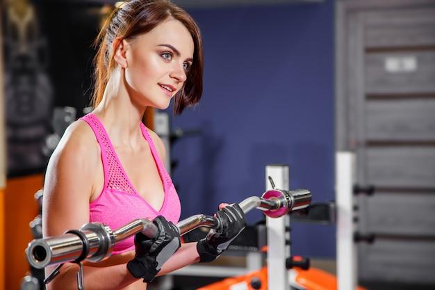 Mujer joven de la aptitud que hace ejercicio con el barbell en el gimnasio