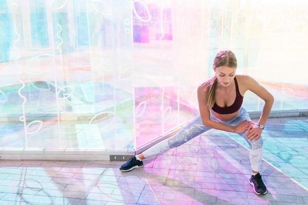 Mujer joven de la aptitud que hace estirando ejercicio en el cuarto