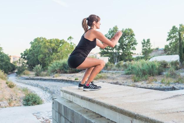 Mujer joven de la aptitud que hace posiciones en cuclillas en el parque