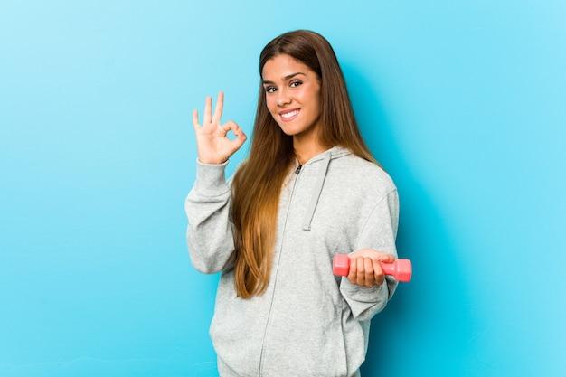 Mujer joven de la aptitud que lleva a cabo un peso alegre y confiado que muestra gesto aceptable.