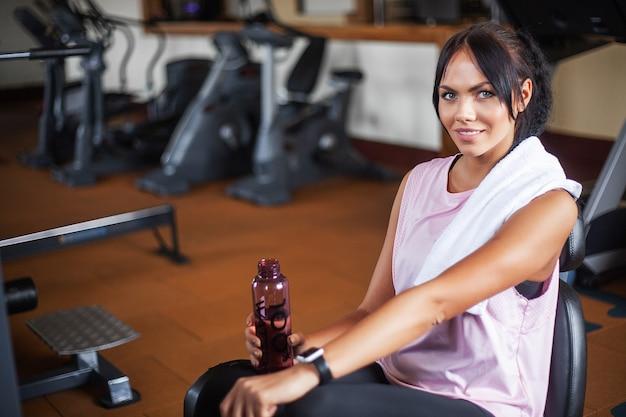 Mujer joven de la aptitud que se resuelve en el gimnasio