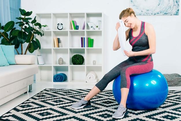 Mujer joven de la aptitud que se sienta en la bola azul de los pilates que limpia sudor con la toalla