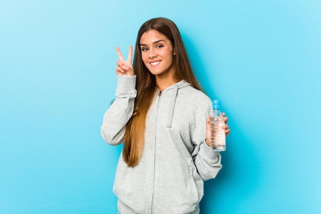 Mujer joven de la aptitud que sostiene una botella de agua que muestra la muestra de la victoria y que sonríe ampliamente.