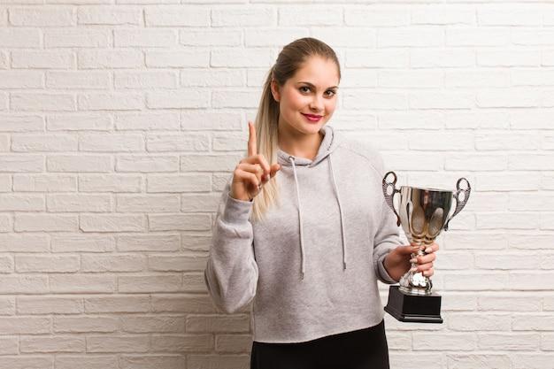Mujer joven de la aptitud rusa que sostiene un trofeo