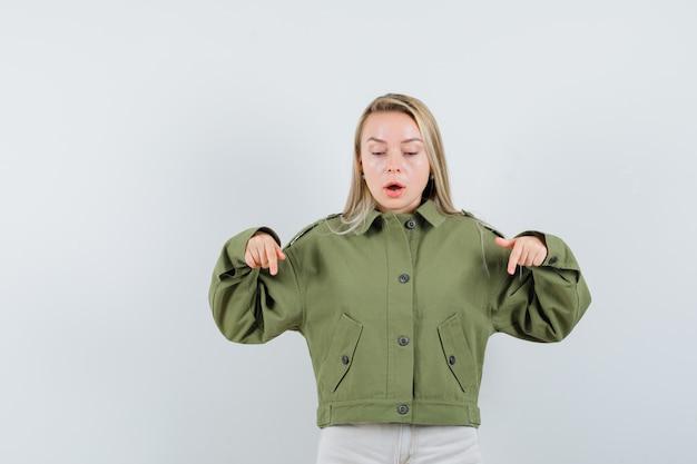Mujer joven apuntando hacia abajo en chaqueta verde, jeans y mirando enfocado, vista frontal.