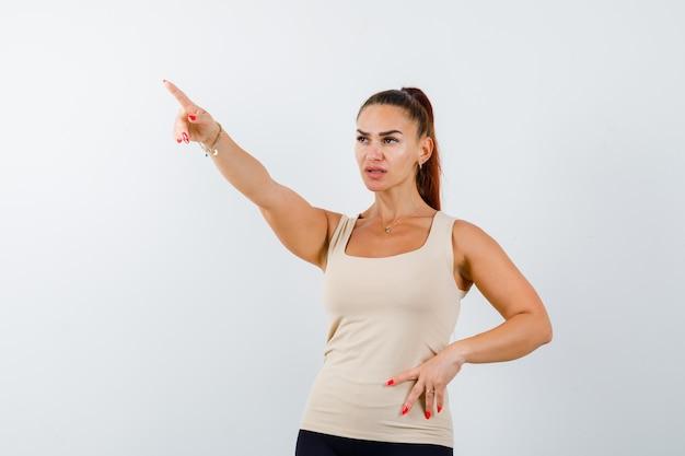 Mujer joven apuntando hacia adelante en camiseta sin mangas beige y mirando confiado. vista frontal.