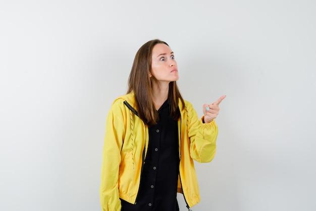 Mujer joven apuntando hacia afuera con el dedo índice