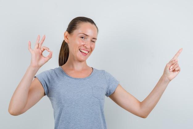Mujer joven apuntando al lado con signo ok en camiseta gris, gafas y mirando contento. vista frontal.