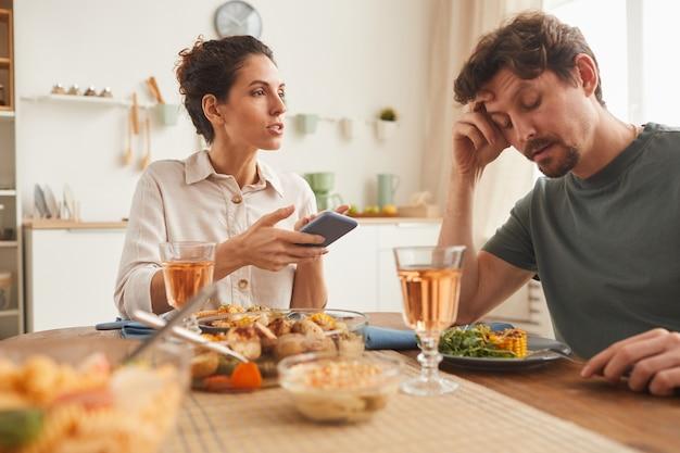 Mujer joven apuntando al teléfono móvil y hablando con el hombre durante la cena en la cocina de casa