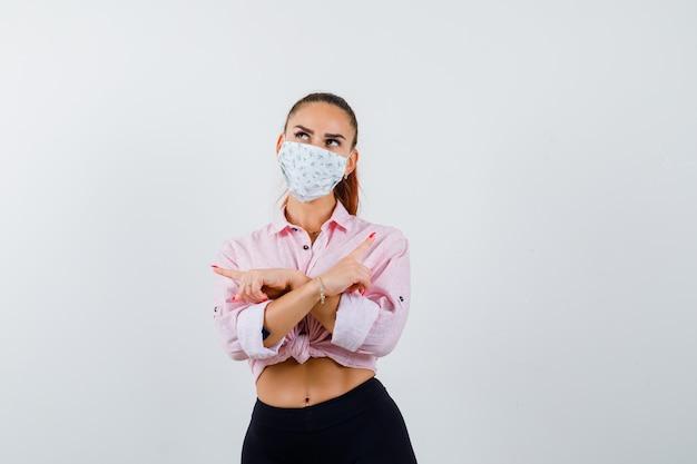 Mujer joven apuntando a ambos lados en camisa, pantalón, máscara médica y mirando vacilante, vista frontal.