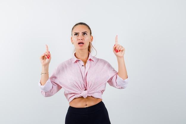 Mujer joven apuntando hacia arriba en camisa casual y mirando desconcertado. vista frontal.