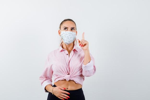 Mujer joven apuntando hacia arriba en camisa, pantalón, máscara médica y mirando pensativo, vista frontal.