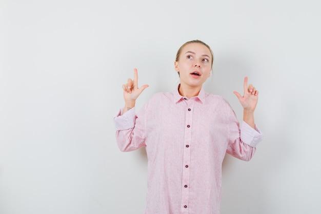 Mujer joven apuntando hacia arriba con camisa rosa y mirando curioso