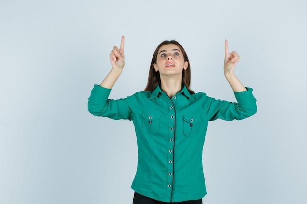 Mujer joven apuntando hacia arriba en camisa verde y mirando esperanzado. vista frontal.