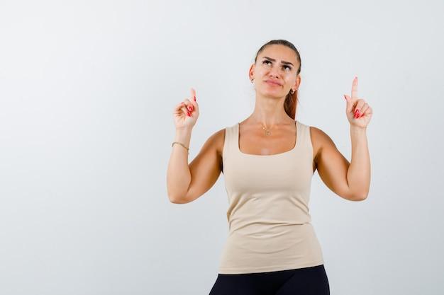 Mujer joven apuntando hacia arriba en camiseta sin mangas beige y mirando pensativo. vista frontal.