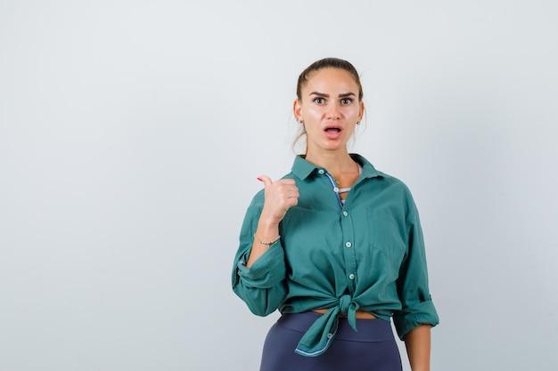 Mujer joven apuntando hacia atrás con el pulgar en camisa verde y mirando sorprendido, vista frontal.