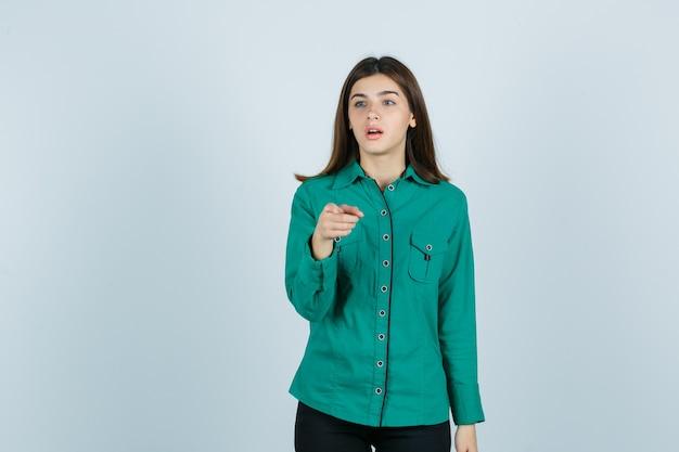 Mujer joven apuntando a la cámara mientras mira a otro lado en camisa verde y mira sorprendida, vista frontal.