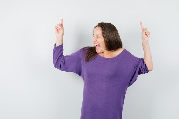 Mujer joven apuntando con el dedo hacia arriba en camisa violeta y con suerte. vista frontal.