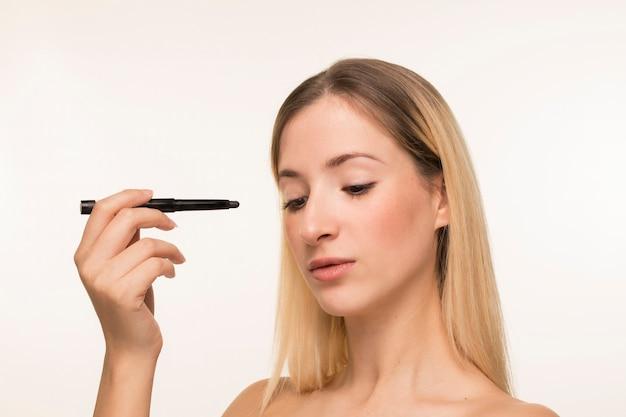 Mujer joven apuntando con delineador hacia su cara