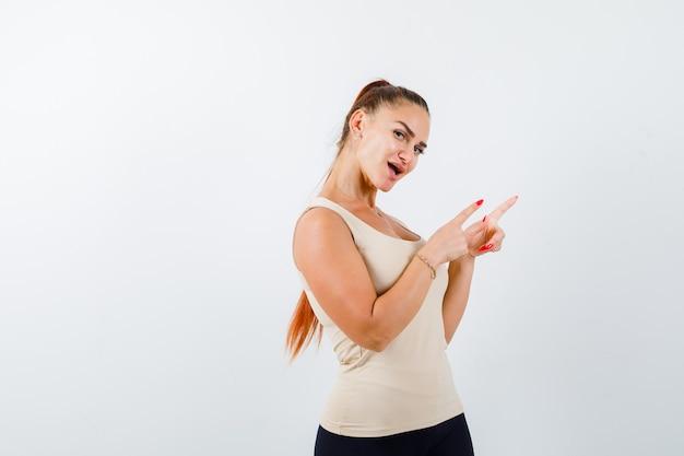 Mujer joven apuntando a la esquina superior derecha en camiseta beige y mirando asombrado. vista frontal.