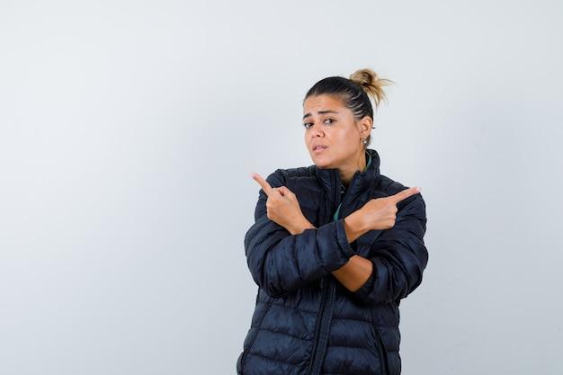 Mujer joven apuntando hacia la izquierda y hacia la derecha en chaqueta acolchada y mirando indeciso. vista frontal.
