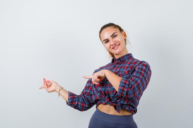 Mujer joven apuntando hacia el lado en camisa a cuadros y mirando feliz, vista frontal.
