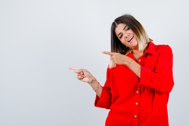 Mujer joven apuntando hacia el lado izquierdo en camisa roja de gran tamaño y mirando feliz. vista frontal.