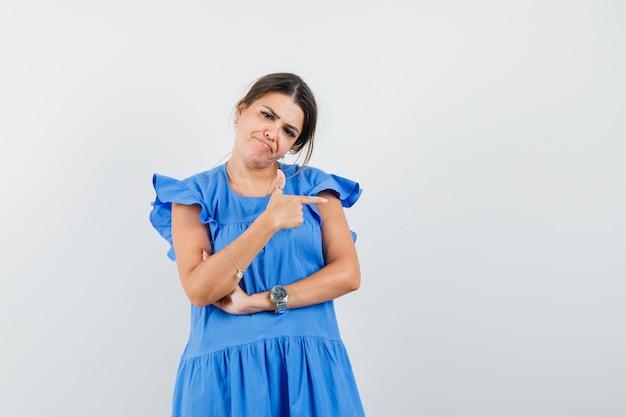 Mujer joven apuntando hacia el lado en vestido azul y mirando desesperado