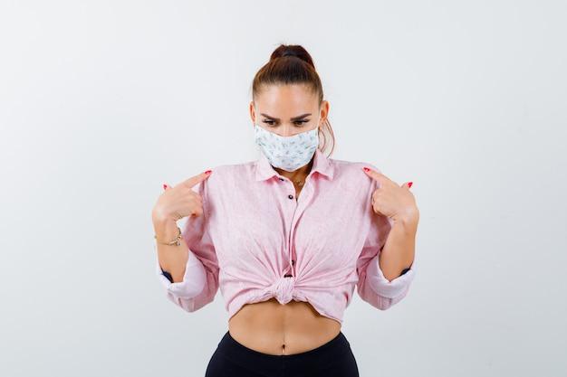 Mujer joven apuntando a sí misma en camisa, pantalones, máscara médica y mirando vacilante, vista frontal.