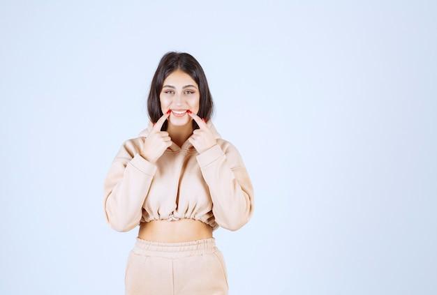 Mujer joven apuntando su boca y significando su sonrisa o higiene bucal