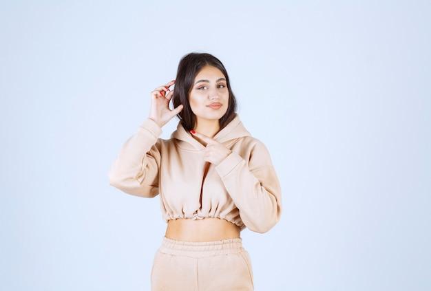 Mujer joven apuntando su oído mientras la voz es alta o baja