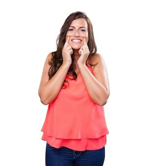Mujer joven apuntando con su sonrisa