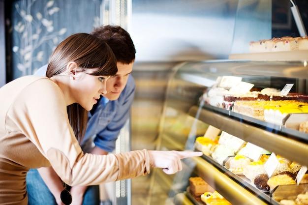 Mujer joven apuntando a tortas en confitería