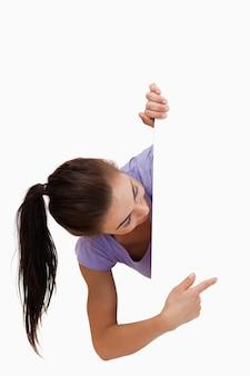 Mujer joven apuntando a la vuelta de la esquina