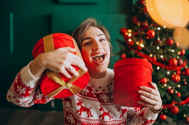Mujer joven con árbol de navidad con cajas rojas