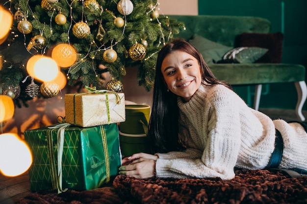 Mujer joven por árbol de navidad desempacando regalos