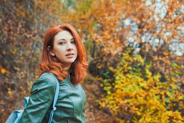 Mujer joven con árbol de otoño