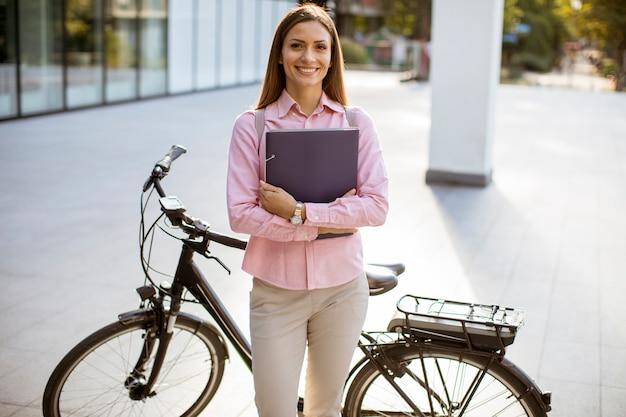 Mujer joven con archivos en las manos de pie al aire libre junto a la bicicleta eléctrica