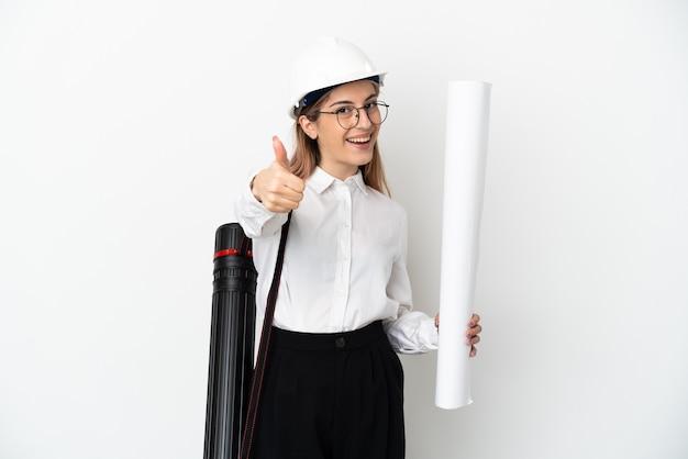 Mujer joven arquitecto con casco y sosteniendo planos aislados en blanco con los pulgares hacia arriba porque ha sucedido algo bueno