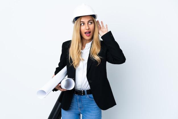 Mujer joven arquitecto con casco y sosteniendo planos sobre blanco aislado escuchando algo