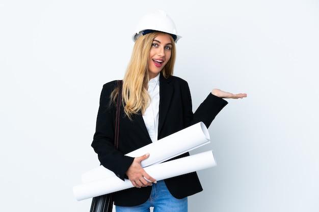 Mujer joven arquitecto con casco y sosteniendo planos sobre blanco aislado extendiendo las manos hacia un lado para invitar a venir