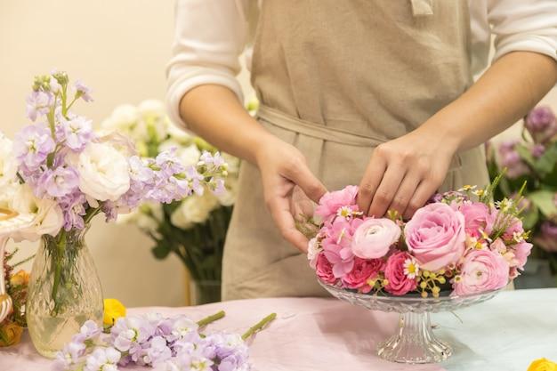Mujer joven arreglando hermoso jarrón de ramo de flores de rosa rosa en la mesa