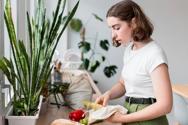 Mujer joven arreglando verduras orgánicas en la cocina