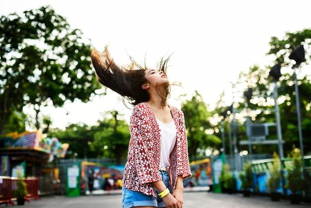 Mujer joven arrojando su cabello en un parque de diversiones