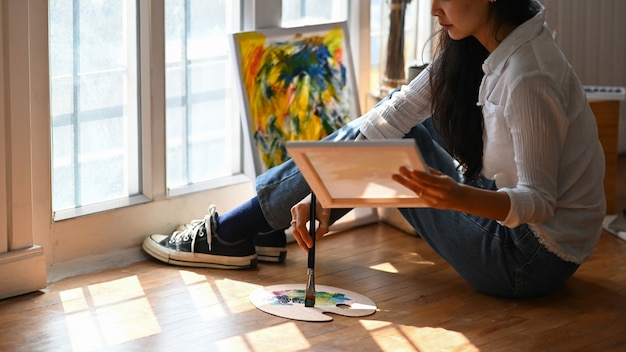 Mujer joven artista dibujando una pintura al óleo mientras está sentado en el piso de madera.