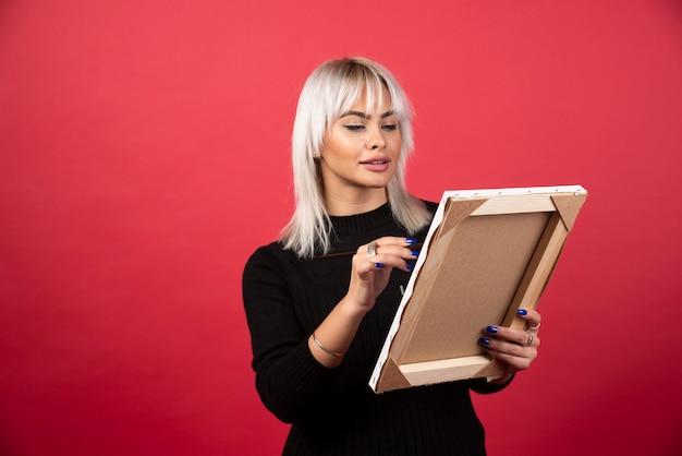 Mujer joven artista dibujo sobre lienzo en una pared roja.