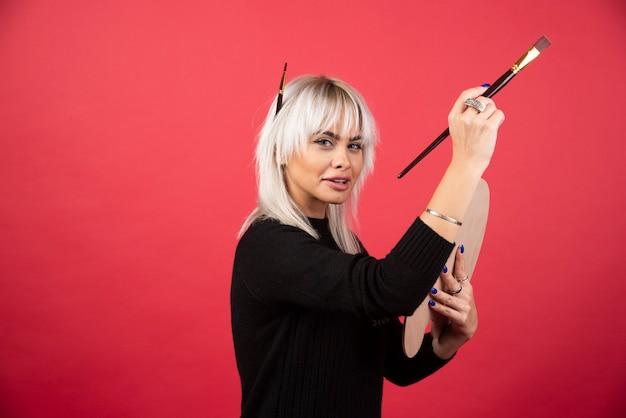 Mujer joven artista sosteniendo material de arte en una pared roja.